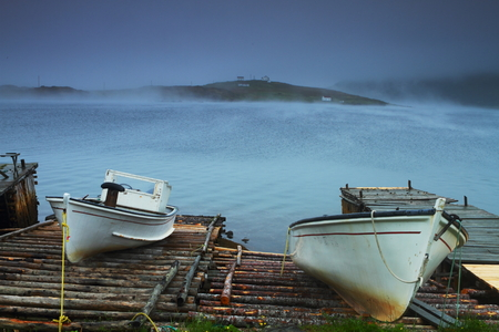 Two old fishing boat on the wooden bridge in misty weather photo