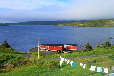 Laundry drying on the clothesline near red cabin in beautiful Nordic landscape photo
