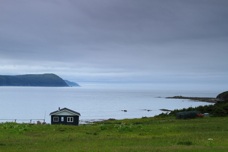Wooden cabin on the shore in Nordic landscape photo