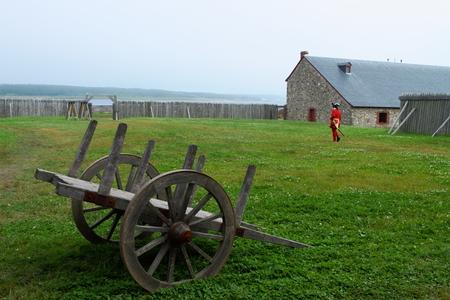 vestidos de epoca: Un hombre vestido con traje rojo de per�odo delante de las fortificaciones anticuado en sitio hist�rico nacional Louisbourg, Nueva Escocia, Canad�