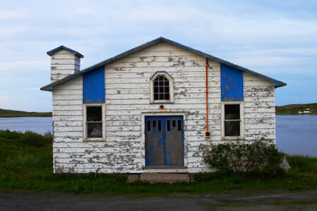 Old weathered white building on the shore photo