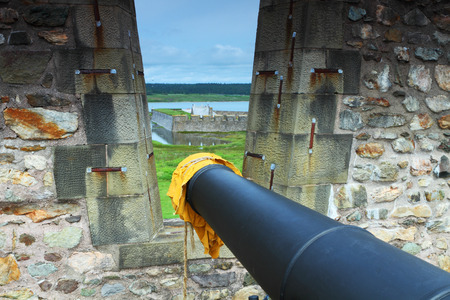 fortified wall: Old cannon?s barrel pointing through a fortified wall in Fortress of Louisbourg, Nova Scotia, Canada