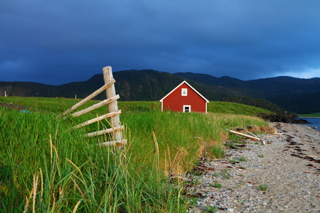 landscape rural: Red wooden cabin on the shore in Nordic landscape Stock Photo