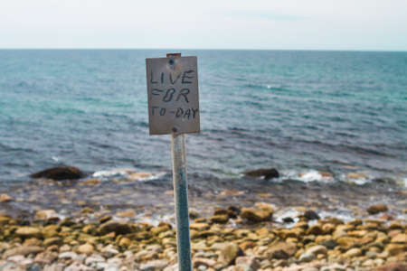 short phrase: The phrase Live for Today is printed on the inspirational signpost on the shore with ocean background