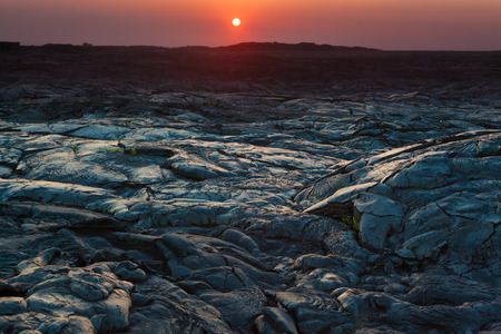 Beautiful sunset over molten cooled lava landscape in Hawaii Volcanoes National Park, Big Island, Hawaii photo