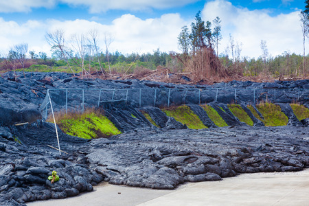 Advancing lava in the town of Pahoa melts and moves through a fence, Big Island, Hawaii