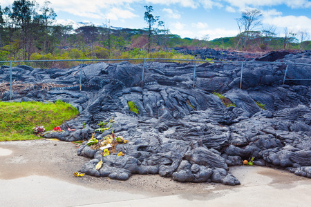 advancing: Advancing lava in the town of Pahoa melts and moves through a fence, Big Island, Hawaii