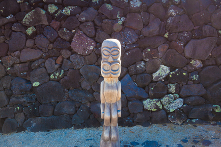 Old wooden protection idol with black lava stone background at an ancient Hawaiian site Pu'uhonua O Honaunau National Historical Park on Big Island, Hawaii