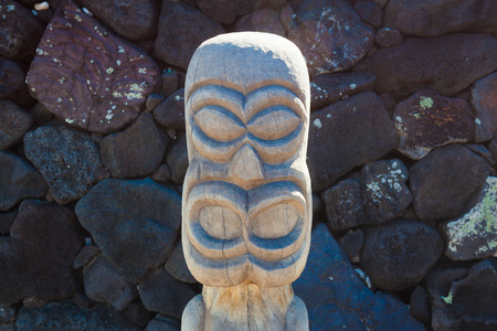 Old wooden protection idol with black lava stone background at an ancient Hawaiian site Puuhonua O Honaunau National Historical Park on Big Island, Hawaii