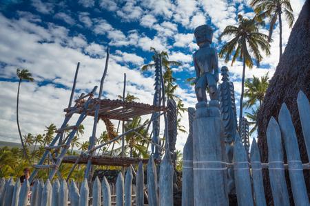Old wooden structures and protection idols at ancient Hawaiian site Pu'uhonua O Honaunau National Historical Park on Big Island, Hawaii Stock Photo