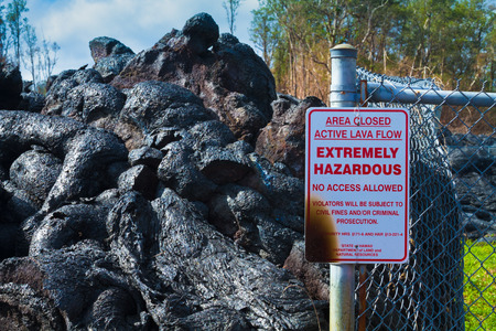 advancing: Warning sign destroyed by advancing lava in the town of Pahoa, Big Island, Hawaii Stock Photo