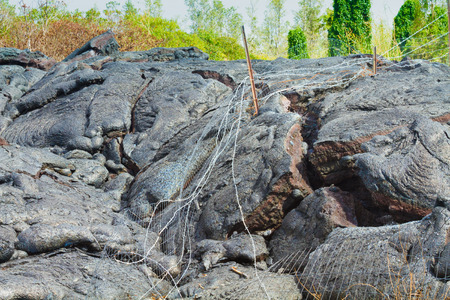 advancing: Wire fence destroyed by advancing lava in the town of Pahoa, Big Island, Hawaii Stock Photo