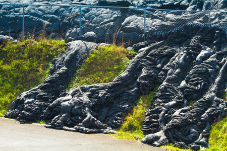 advancing: Advancing lava flow through the fence in the town of Pahoa, Big Island, Hawaii