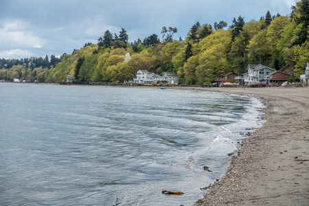 pacific northwest: Small waves ripple toward shore at Dash Point Washington. Homes sit under lush green trees as Spring erupts in the Pacific Northwest.