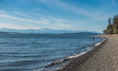 A view of a fisherman and the Olympic Mountains from Lincoln Park in West Seattle, Washington. Stock Photo