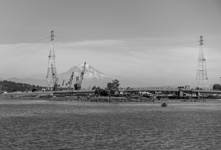 tacoma: Majestic Mount Rainier is in the distance behind power lines and equipement. Black and white image.