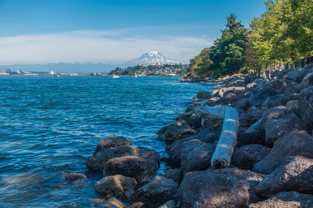 Rocks line the shore in Ruston, Washington. Mount Rainier can be seen in the distance. Stock Photo