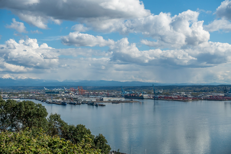 View of the Port Of Tacoma on a sunny day. Puffy clouds are reflected in the calm waters of the Puget Sound. Stock Photo