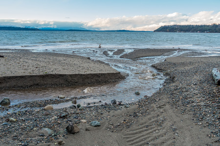 puget: A stream flows across the shoreline at Seahurst Park on its way to the Puget Sound. Photo take in Burien, Washington. Stock Photo