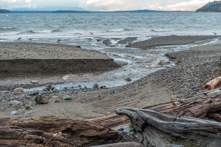 shorelines: A stream flows across the shoreline at Seahurst Park on its way to the Puget Sound. Photo take in Burien, Washington. Stock Photo