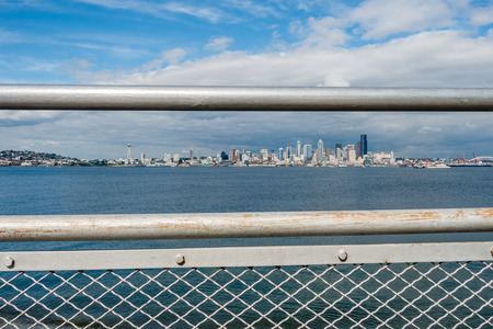 Metal railings frame the Seattle skyloine and part of Queen Anne Hill. Shot taken from Alki Beach.