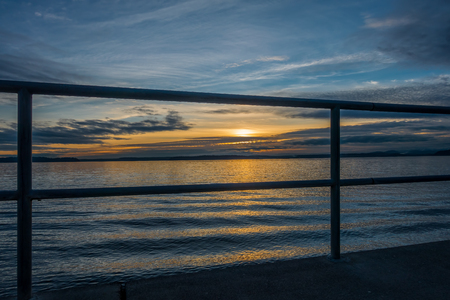 puget: Looking through a fence at a sunset over the Puget Sound from West Seattle. Stock Photo