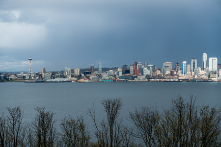 The Seattle skyline is bathed in partial sunlight as rain clouds threaten. West Seattle trees fill the forground. Stock Photo
