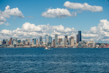 elliot: White puffy clouds hover over the Seattle skyline on a sunny day.