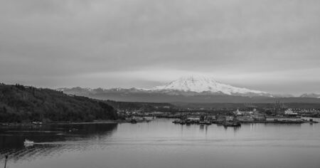 tacoma: Clouds cover the top part of a snow-laden Mount Rainier. Port of Tacoma is below.