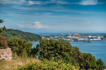 Clouds hover near Mount Rainier with the Port of Tacome below. Stock Photo