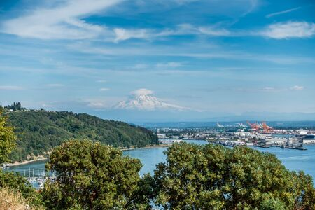 tacoma: Clouds hover near Mount Rainier with the Port of Tacoma below. Stock Photo