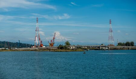 Mount Rainier rises up behine power lines at the Port of Tacoma. Stock Photo