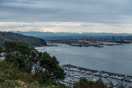 Majestic Mount Rainier is partially covered with clouds. Marina in the Port Of Tacoma is seen in the foreground. Stock Photo