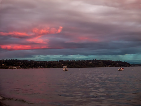 Two boats are anchored at Three Tree Point, Washington as the sun sets.  A pink and purple sky blankets the Puget Soiund.