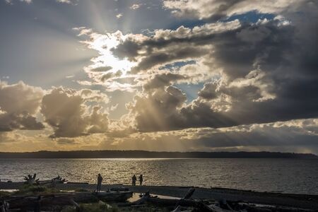 Clouds obscure the sun creating rays of light over the Puget Sound. Stock Photo