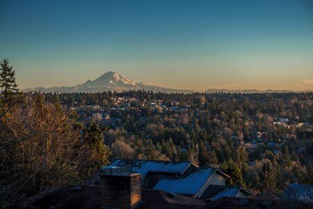 A veiw of Mount Rainier on a clear winter day with homes in the forefround. Shot taken from Burien, Washington. Stock Photo