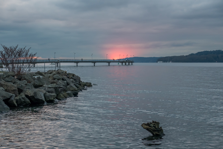 A section of the horizon flares up in red as the sun sets behind the clouds in Des Moines, Washington. Stock Photo
