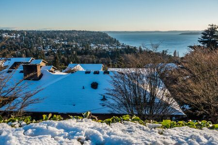 puget: Snow cover roofs of home in Burien, Washington. The Puget Sound can be seen in the distance.
