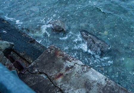 Water of the Puget Sound splashes on shoreling rocks next to a sea wall. Banco de Imagens