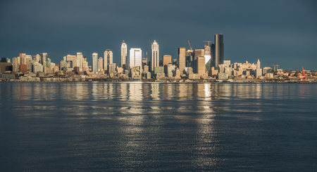 As the sun sets the buildings of the Seattle skyline are relfected in Elliott Bay.
