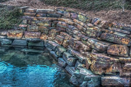 HDR image of a wall by a pond that looks radioactive. HDR image. Imagens