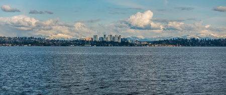 Panorama shot of the skyline of Bellevue, Washington with the Cascade Mountains behind.