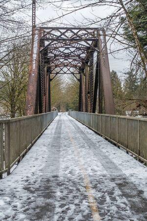 Snow covers a bridge and trestle that spans the Cedar River in Renton, Washington. Stock Photo