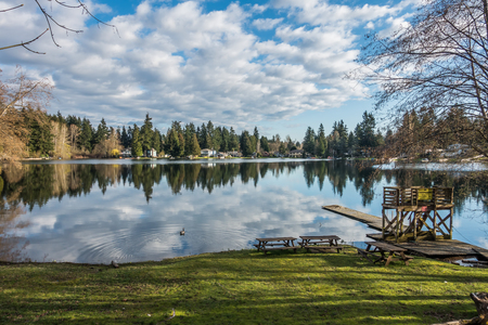 Homes, trees and sky are reflected in the water of Mirror Lake in Federal Way, Washington. Stock Photo