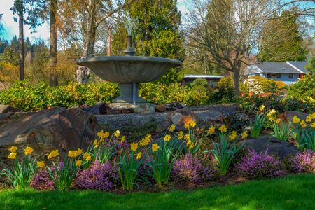 northwest: A view of Spring flowers and a cement fountain in Normandy Park, Washington. HDR image.