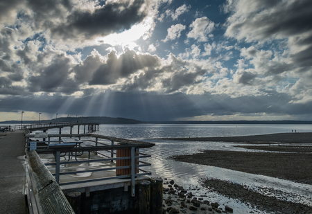 puget: Rays of sunlight break through the clouds over the pier at Des Moines, Washington.