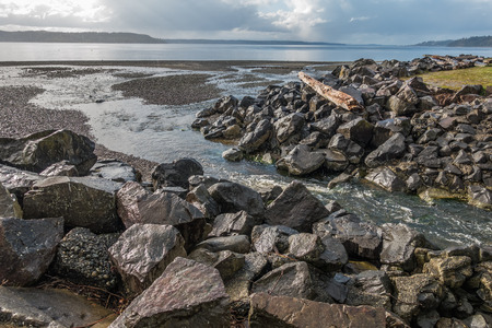 puget: A creek flows past boulders into the Puget Sound at Saltwater State Park in Des Moines, Washington.