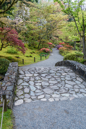 A rock bridge leads to blooming flowers in a Seattle garden. Stock Photo