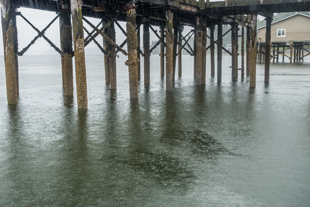 A view from beneath the pier in Redondo Beach , Washington. It is raining.