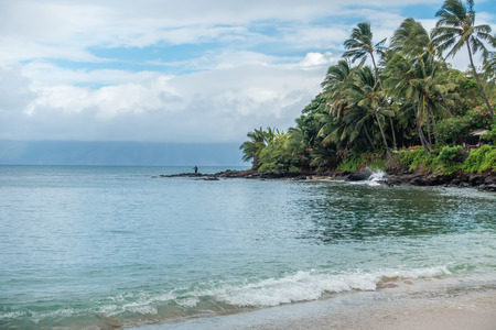 A lone fisherman tries his luck on a beach in the Kahan area of Maui, Hawaii. Stock Photo